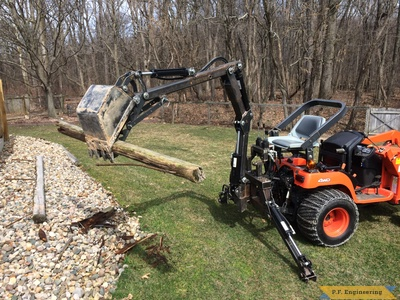 Kubota BX2200 micro hoe picking up log with thumb by Mark J.